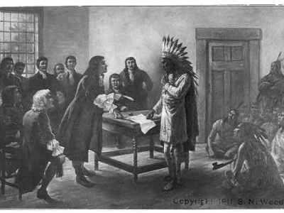 """A black and white drawing depicting King (Metacomet) Philip, a Wampanoag man in a feathered headdress, long-sleeved thigh-length tunic, soft shoes, and cloak with one hand on a document on a table to his right. He is looking at a white man who leans forward with one hand on the table and a quill extended towards Philip. The white man is wearing a long open coat, a cravat, and boots. Behind Philip on the image's right, five other Indians sit on the floor and two stand, one with crossed arms by the door. Around the central white man, two white men sit on chairs in the left foreground and eight others sit and stand in the background in front of a large paned window. Philip is drawn in greatest detail with the most intricate shading, making him stand out. On the bottom right reads """"Copyright [illegible] S. N. Wood."""""""