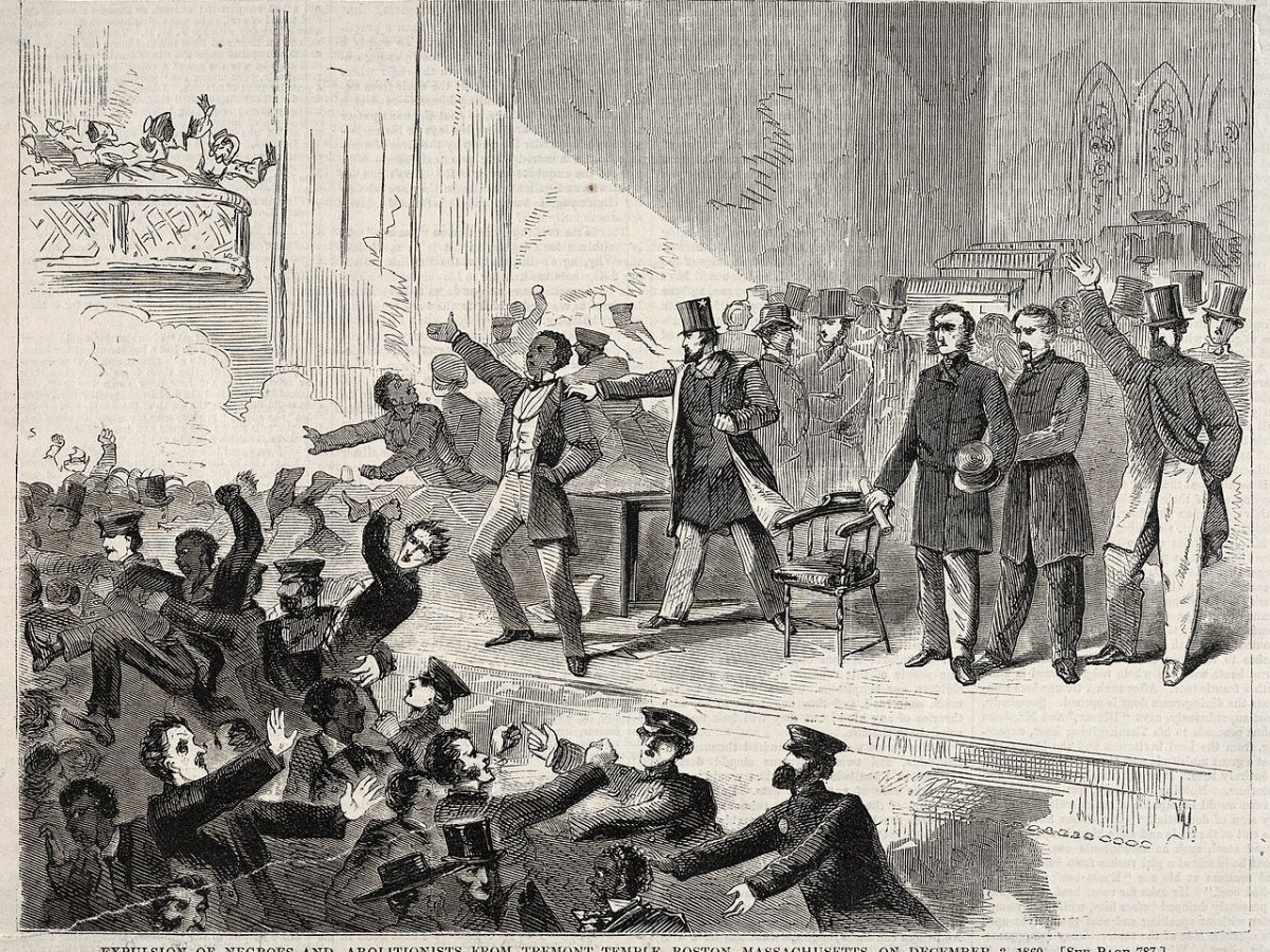 A black and white wood engraving print of an abolitionist meeting in Tremont Temple in Boston, MA on December 3, 1860. Frederick Douglass, a Black man, wears long pants, a waistcoat, and a long coat on the stage in the center of the image. He stands with one hand on his hip and the other out-raised, his mouth open as he speaks back to an unruly crowd at the lower left and in the background around the stage. Officers attempt to quell the crowd in the bottom center of the image. A white man on stage steps towards Douglass and has his hand on Douglass's shoulder. Other white men stand on stage looking at the crowd. On the far right midground, a white man with a beard in a top hat, long pants, and knee-length coat has his left hand in his pocket and his right hand up. In the upper left of the image, three women in bonnets fight on a jutting balcony.
