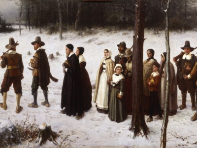 A painting of a group of fifteen puritans in 17th century dress walking through a snowy field. In the extreme are three skinny trees. In the distance are more trees.