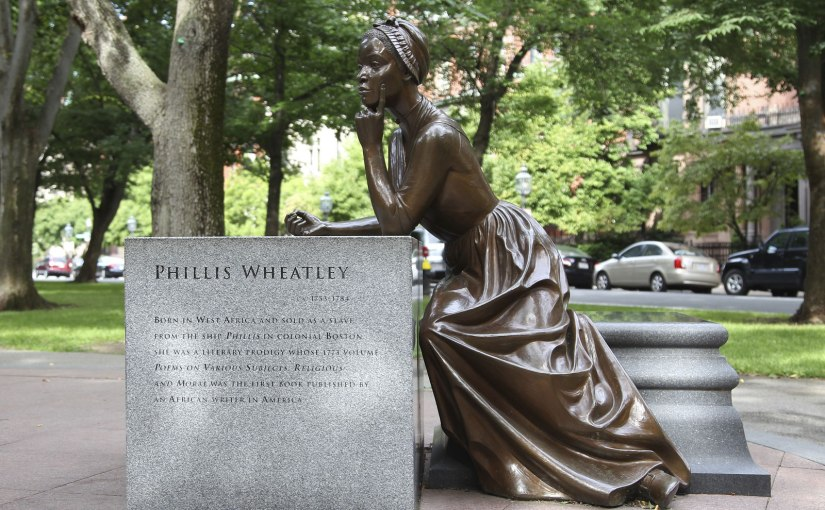 A bronze statue of Phillis Wheatley is sitting sideways on a granite bench and leaning on a large granite block. She is wearing a long dress and wearing a bonnet. Her left hand is propped against her chin and she is holding a quill in her right hand.