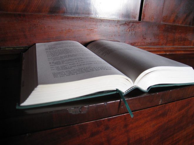 A green hardcover book lies open on a wooden shelf. A green ribbon bookmark sticks out of the bottom of the book.