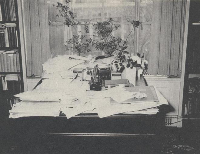 A black and white photograph of a desk in front of a window covered in a spread of loose papers, books, and a few potted plants.