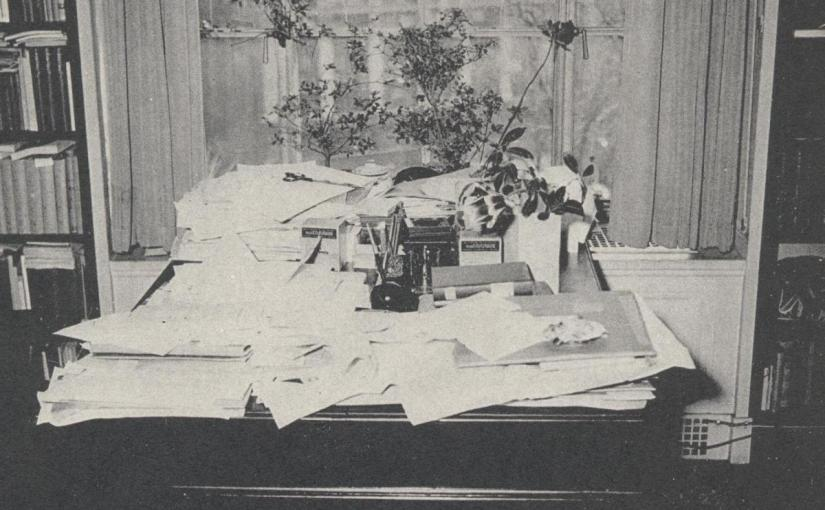 A black and white photograph of a Walter Muir Whitehill's desk. The desk is covered in loose papers.